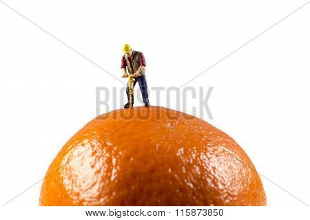 Miniature Worker On Top Of An Orange