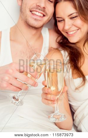 Cheers! Couple In Love Celebrate Honeymoon With Champagne On The Bed
