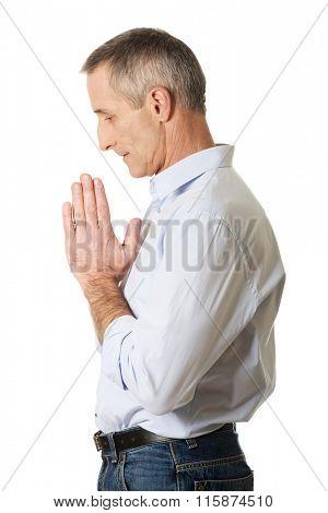Mature man praying to God