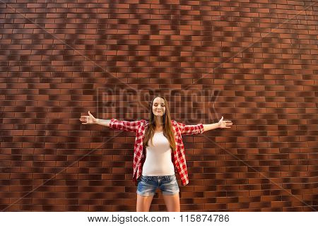 Young Girl Standing With Opened Hands On The Bakground Of Brik Wall