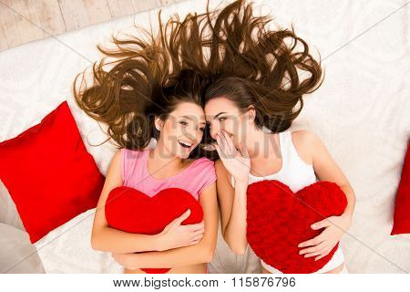 Cheerful Beautiful Girls In Pajamas Gossiping And Lying On The Bed Holding Pillows