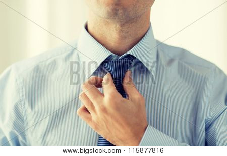close up of man in shirt adjusting tie on neck