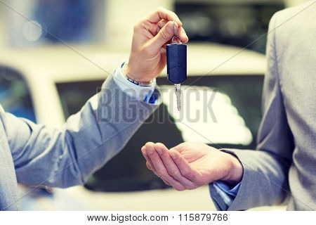 close up of male hands with car key in auto salon