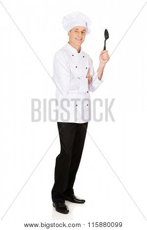 Chef holding black plastic spoon