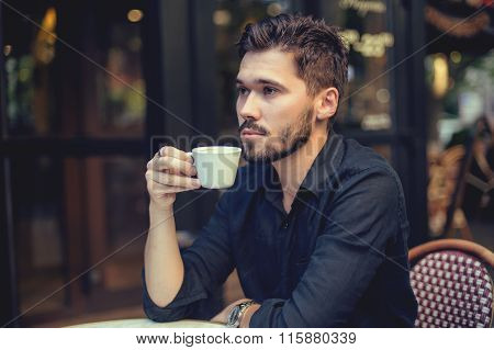 Cutie man with cup of coffee looking at mobile phone outdoors