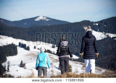 Three girls enjoying mountain view together in wintertime.