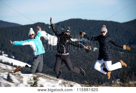 Three girls jumping together in wintertime. Mountain background
