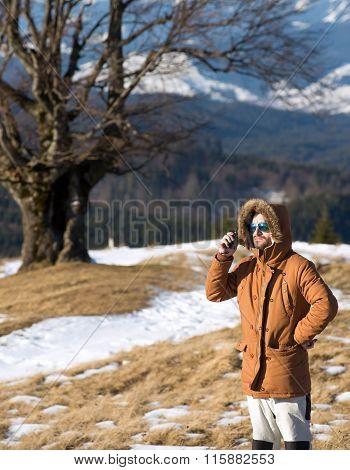 Male hiker using walkie talkie against mountain peaks