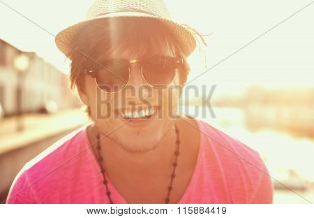 Happy man in hat and sunglasses smiling at the beach on the sunset