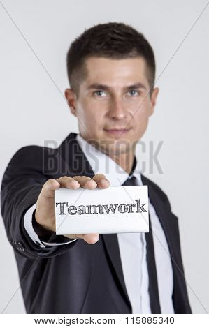 Teamwork - Young Businessman Holding A White Card With Text