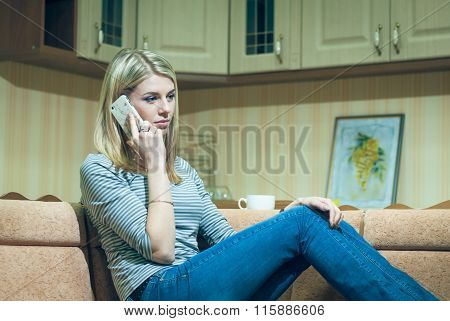 Young woman sitting alone and talking on phone