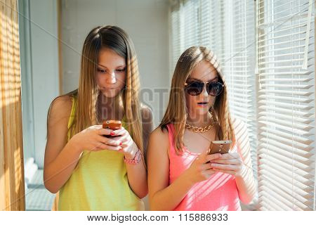 Two teenage girls looking in their gadgets