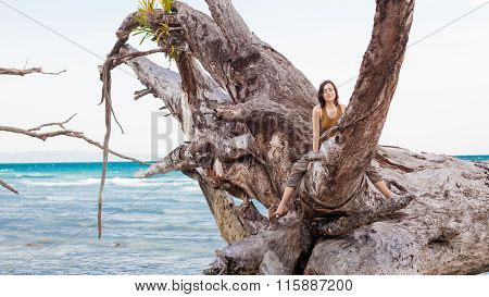 Woman In Alladin Pants Is Relaxing On The Giant Roots