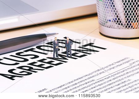 Tiny businessman dolls and contract