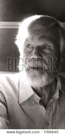 Senior Man With Beard Conversing In Restaurant