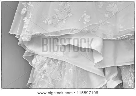 A Black And White Photo Of A Detailed White Wedding Dress With White Flowers And Fake Diamonds