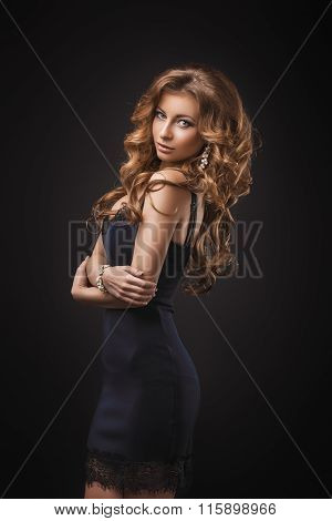 Portrait of wonderful young blonde woman with long hair looking at camera. Sexy girl in blue dress.
