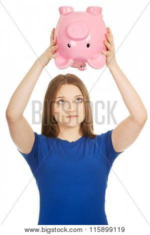 Teenage woman shaking piggybank.