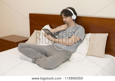 casual man working with a tablet pc in bed