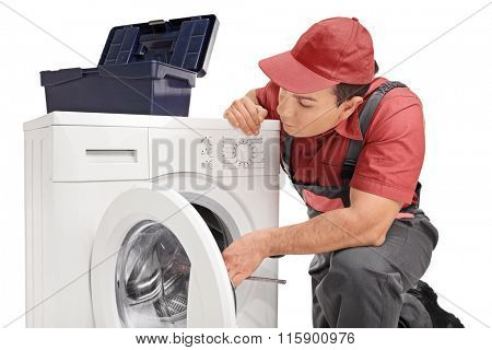 Studio shot of a young repairman fixing a washing machine isolated on white background