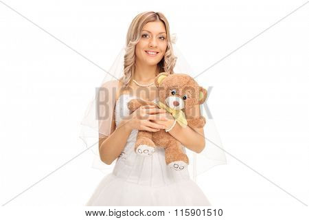 Young cheerful bride holding a teddy bear and looking at the camera isolated on white background