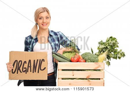 Female agricultural worker holding a cardboard sign that says organic and leaning on a crate full of vegetables isolated on white background