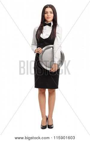 Full length portrait of a young waitress holding a round metal tray and looking at the camera isolated on white background