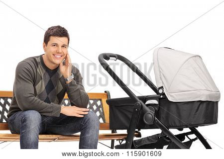Young father sitting on a bench with a baby stroller next to him isolated on white background