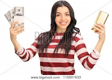Studio shot of a joyful woman holding a few stacks of money and a gold bar isolated on white background