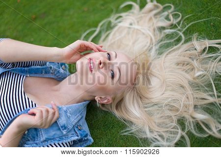 Woman Lying On The Green Grass With Untressed Hair