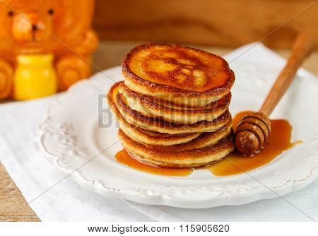 Breakfast. Fritters with honey  on a white plate.  Homemade pancakes.  Selective focus