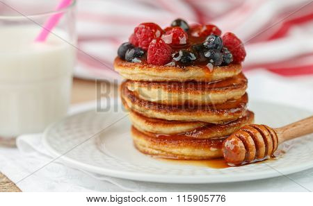 Breakfast. Fritters   with honey and berries - raspberries and blueberries on a white plate