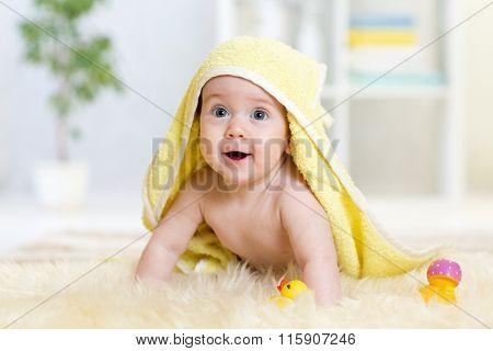 happy baby under towel indoor after bathing