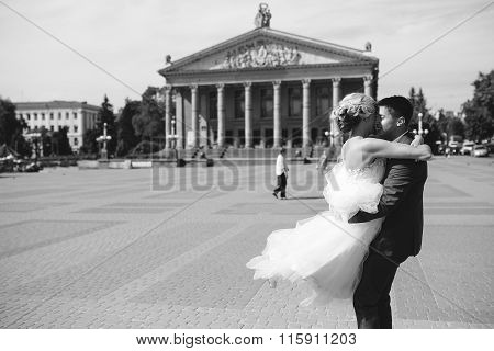 groom holds bride in his arms and twisted