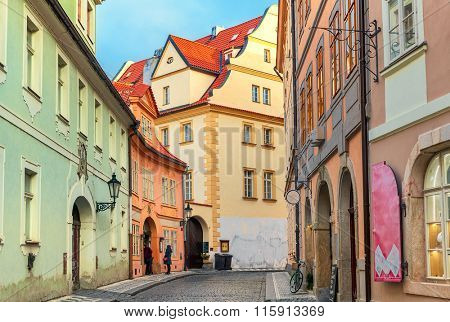 Narrow cobblestone street among typical colorful houses in Old Town of Prague, Czech Republic.