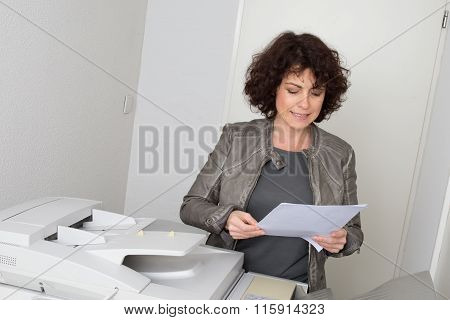 Female Secretary Working In Office, Copying Document And Paperwork