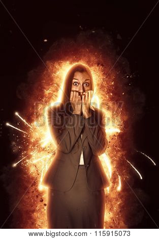 Panic stricken young Indian businesswoman surrounded by burning flames staring wide-eyed at the camera and biting her nails in a conceptual image over a dark shadowy background