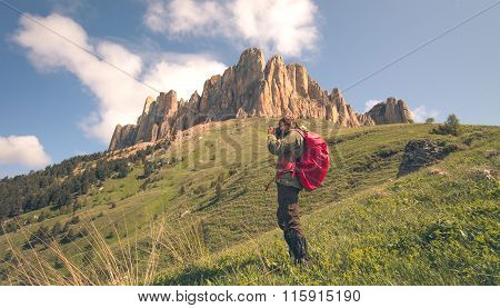 Man Traveler with photo camera and backpack hiking outdoor