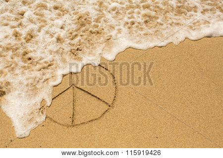 Pacific - sign of peace painted on the beach sand, soft wave.