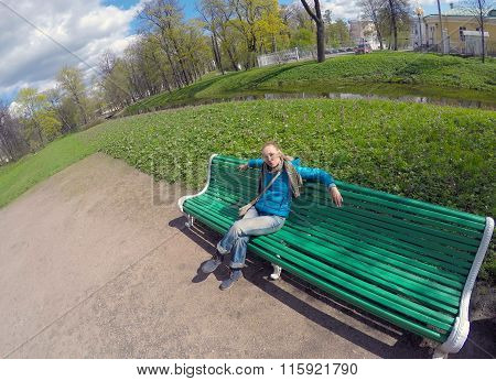 The woman in a blue jacket on a bench in park in the spring