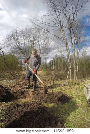 The young man digging ground and preparing for planting on the wet soil in the early spring