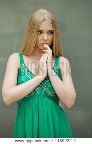 Portrait of a beautiful young blonde in green dress