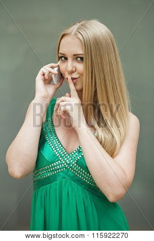 Portrait of attractive girl with finger on lips, concept of student show quiet, silence, secret gesture, young pretty blonde woman in green dress