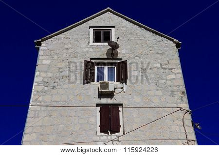 Brickwork House With Open Window Against Blue Sky.