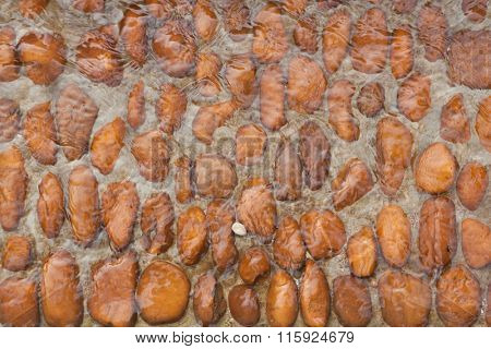 Water flowing over river rounded orange pebbles. Background texture.