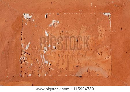 Traces of old announcements seen on terracotta painted stucco wall. Background texture.