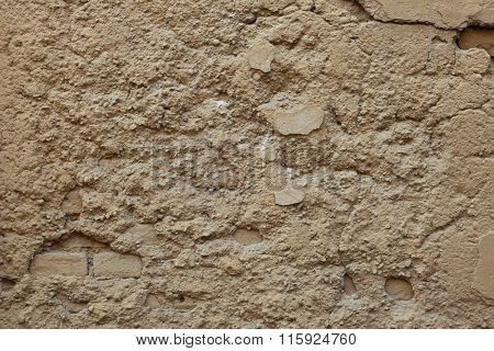 Old ochre painted stucco wall with cracked plaster. Background texture.