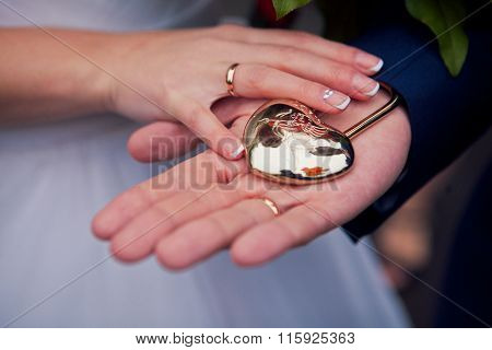 the couple holding hands in a heart-shaped lock