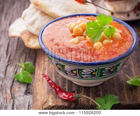 Cream soup puree of roasted tomatoes and peppers served with chickpeas cilantro