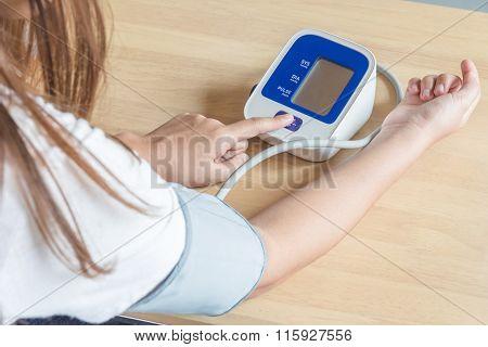 Female Press Start Button On Blood Pressure